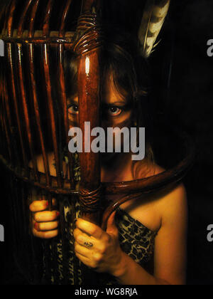 Portrait Of Girl In Tribe Costume Looking Through Wooden Shield At Night - Stock Photo