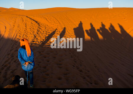 Camels caravan shadows projected over Erg Chebbi desert sand dunes at Morocco - Stock Photo