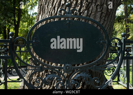 Empty blank sign on metal forging fence in front of big tree. Mock up of information table placard to add any text of symbols. Signboard in park or bo - Stock Photo