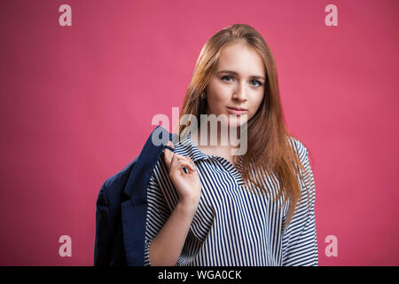 Horizontal portrait of a beautiful red haired student girl on a pink background. A young woman wears a striped blouse and throws a jacket behind her b - Stock Photo