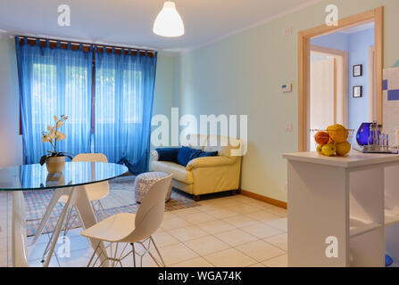 Stylish living room of a small apartment, with a round modern glass table and a part of the kitchenette visible on the right - Stock Photo