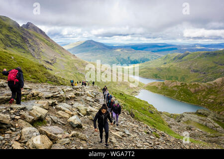 People walking up worn eroded Pyg Track busy route to Mt Snowdon above Glaslyn in mountains of Snowdonia National Park. Llanberis Gwynedd Wales UK - Stock Photo