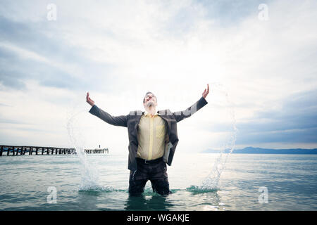 Young Man Wearing Suit While Standing In Sea Against Sky - Stock Photo