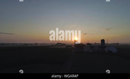 An Aerial View of a Sunrise Over an Amish Farm with Blues and Reds on a Clear Summer Morning - Stock Photo