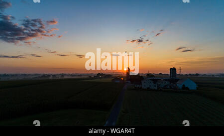 An Aerial View of a Sunrise Over an Amish Farm with Blues and Reds With a Hot Air Balloon Floating By on a Clear Summer Morning - Stock Photo