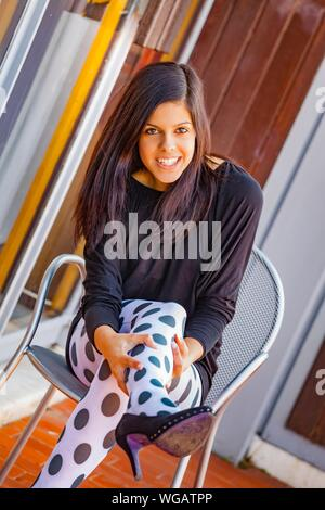Teen girl giggling laughing smiling pulling dot patterned opaque pantyhose on legs leg high-heels raised up upwards - Stock Photo