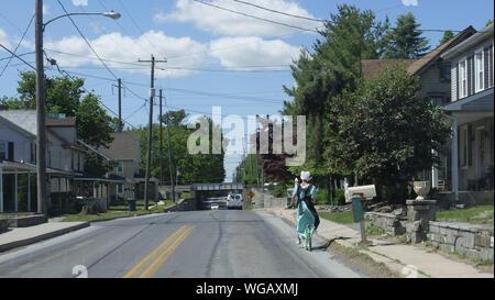 An Amish Girl riding a Scooter on a Public Road on a Sunny Summer Day - Stock Photo