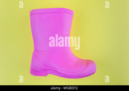 kids pink rubber boots EVA on a yellow background. - Stock Photo