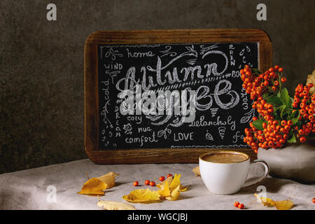 Cup of espresso coffee and vintage chalkboard handwritten lettering on linen table cloth with yellow autumn leaves and berries in ceramic vase. Dark w - Stock Photo
