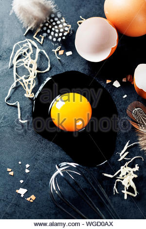 Fresh eggs with straw and  feathers  on a dark background - Stock Photo