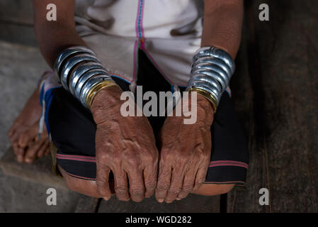 Low Section Of Senior Woman Wearing Bangles While Sitting On Wooden Floor - Stock Photo