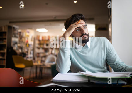 People, education, studying, exams and school concept - tired student learning in library - Stock Photo