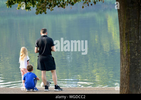 Young Family feeding the birds on Serpentine lake, Hyde Park, London, United Kingdom - Stock Photo