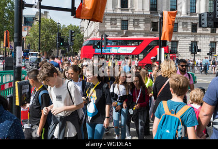 Crowded pavement and crowds of people walking across a pedestrians crossing in the City of Westminster, City of London, UK. Hustle and bustle. - Stock Photo