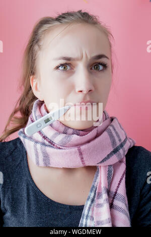 Flu cold grippe. Woman having high temperature. Sick girl with fever checking mercury thermometer on pink background. - Stock Photo