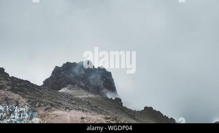 Low Angle View Of Smoke Emitting From Mountains Against Sky - Stock Photo