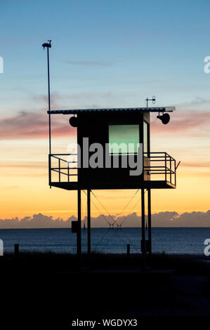 Scenic View Of Silhouette Lookout Tower On Beach Against Cloudy Sky - Stock Photo
