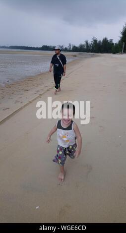 Portrait Of Happy Girl On Beach Against Sky - Stock Photo