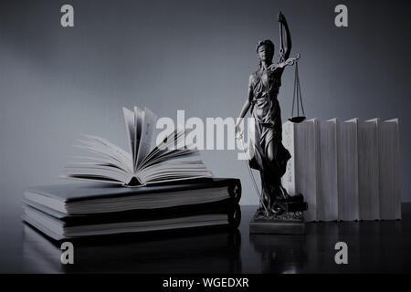 Close-up Of Books And Lady Justice Figurine On Table Against Gray Background - Stock Photo