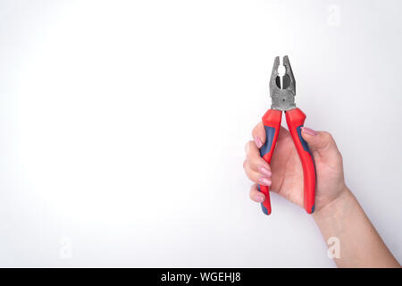 Fashion woman's hand with a gentle manicure holds a tool. Safe work, place for an inscription. View from above. White background, contrasting shadow. - Stock Photo