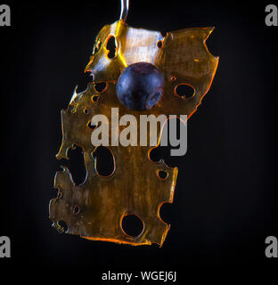 Close up detail of marijuana oil concentrate aka shatter isolated on black background with blueberry - Stock Photo