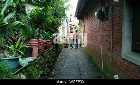 Rear View Of Old Couple Walking Past House - Stock Photo
