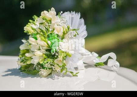 Flowers Bouquet On Decorated Wedding Car Roof - Stock Photo