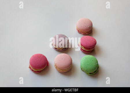 Colorful macaroon cakes triangle shaped composition isolated on white background - Stock Photo