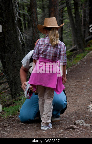 Man Wearing Shoes To Daughter In Forest - Stock Photo