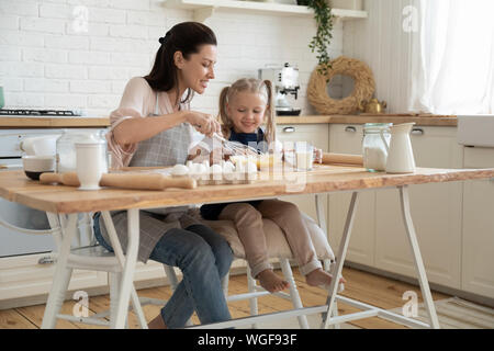 Little helper and mother cooks pie together in kitchen - Stock Photo