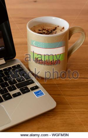 Flag of Uzbekistan on Personal coffee cup next to laptop, Blandford, Dorset, England, UK - Stock Photo