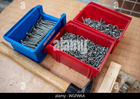 on the table are different coloured boxes filled with screws and next to them is a hammer - Stock Photo