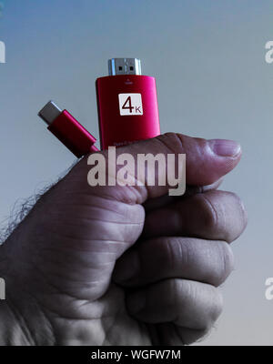 Close up of a man's left hand holding a usb type c to hdmi cable with 4K and type c writing on the hdmi piece. - Stock Photo