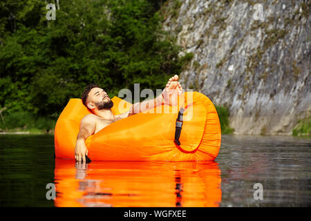 The businessman fell asleep in a raft drifting along the river and dropped his hand with the phone clasped in it into the water. Water got inside the - Stock Photo