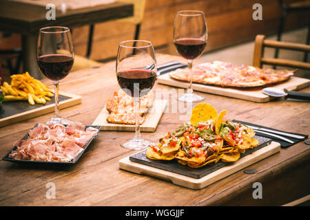 High Angle View Of Various Food By Red Wine In Glasses Served On Wooden Table - Stock Photo
