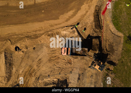 Drone top down view of construction site and excavator excavating soil. - Stock Photo