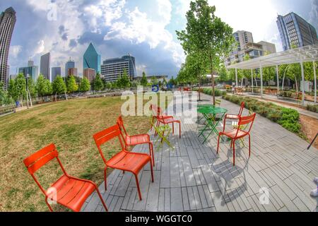 Empty Chairs On Footpath In Garden By Modern Buildings Against Sky