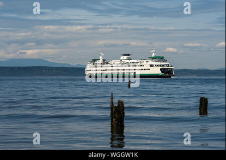 Edmonds Ferry leaving Edmonds Ferry Terminal into Puget Sound with wood pilings in foreground - Stock Photo