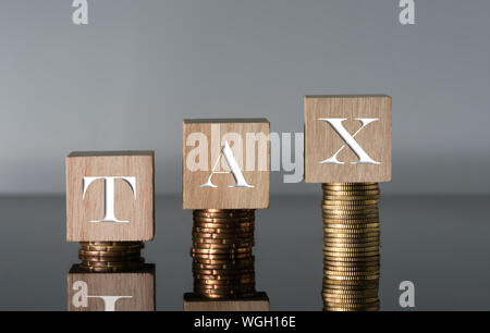 Close-up Of Wooden Blocks With Tax Text On Stacked Coins Against Gray Background - Stock Photo