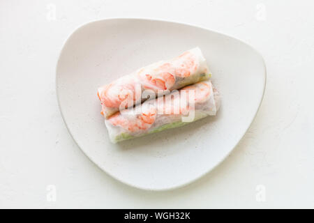 top view of Nem cuon (fresh Vietnamese nem roll with shrimps, mango and ginger) on white plate on white board - Stock Photo