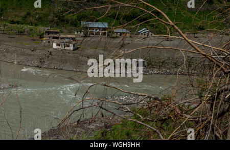 Panoramic view of the village beside river in himalayas - Stock Photo