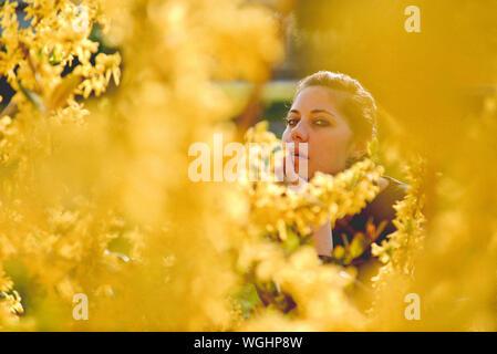 Portrait Of Woman Seen Through Flowering Plants - Stock Photo