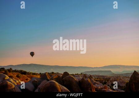 Hot Air Balloon Flying Over Landscape Against Sky - Stock Photo