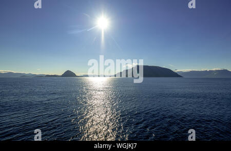 rocky peaks rise out of the sea, sunshine, blue sky, shiny sea water, Godøya, Møre og Romsdal, Norway, Scandinavia, Europe, NOR, travel, tourism, dest - Stock Photo