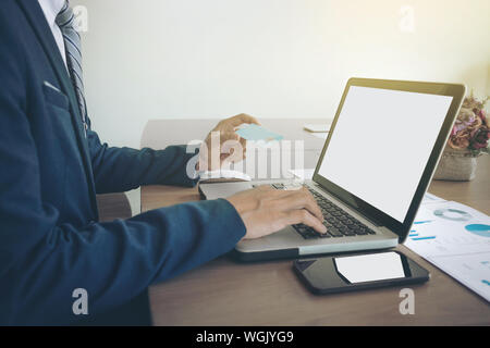 Close-up Of Businessman Making Online Payment While Using Laptop On Desk At Office - Stock Photo
