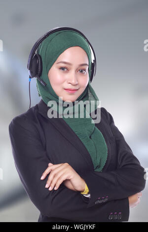 Portrait Of Confident Businesswoman With Headphones Wearing Hijab At Call Center - Stock Photo