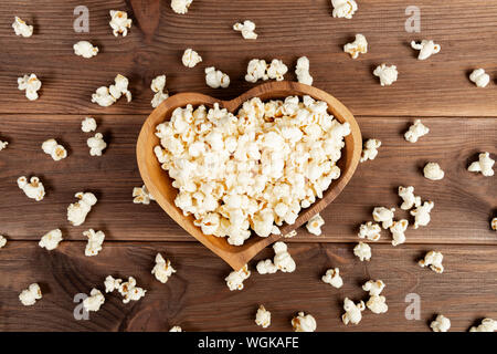 Popcorn in a brown wooden plate in the shape of a heart on a wooden table. Popcorn is laid out on the table