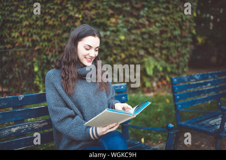 Young woman in a sweater reading a book, sitting on the bench in the park. Autumn time. - Stock Photo
