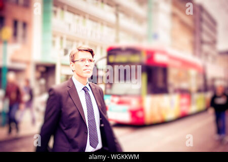 Close-up Of Businessman Walking On City Street - Stock Photo