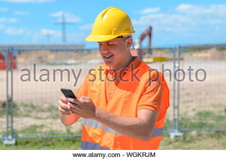 Construction Worker Using Mobile Phone At Site Against Sky - Stock Photo